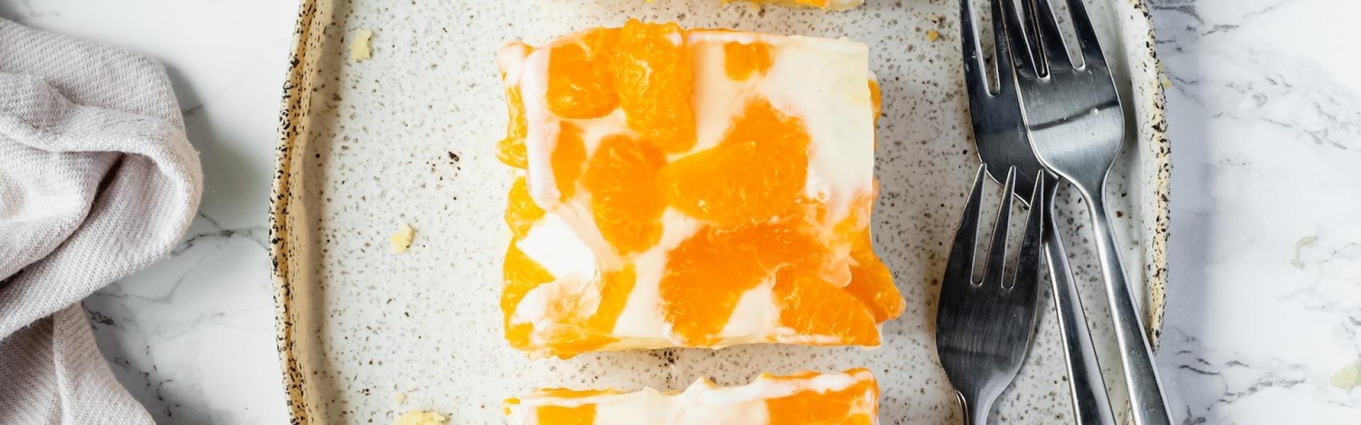 Drei Stücke Mandarinen-Joghurt-Kuchen auf einem Teller mit angelehnten Gabeln.