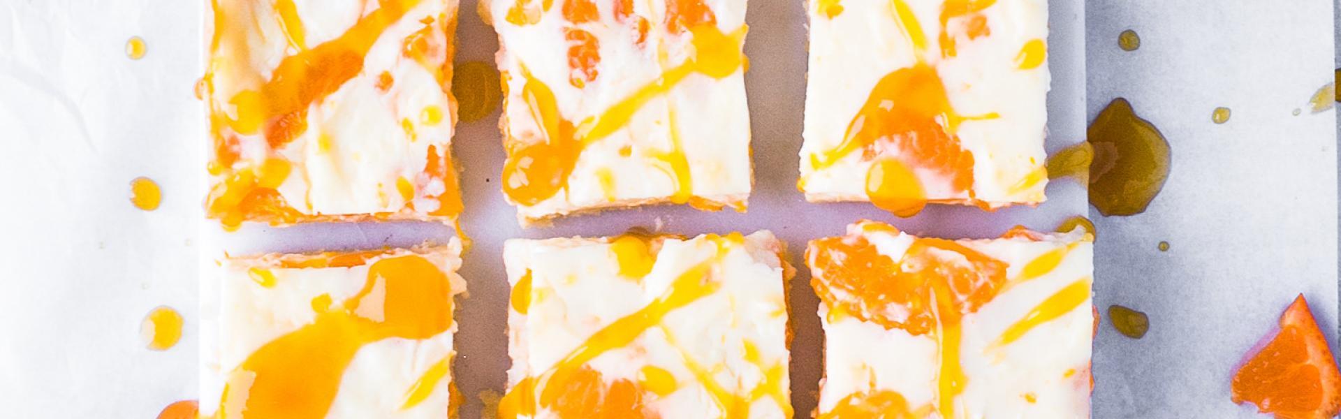 Mandarinen-Schmand-Kuchen vom Blech in Stücke geschnitten auf weißer Platte.