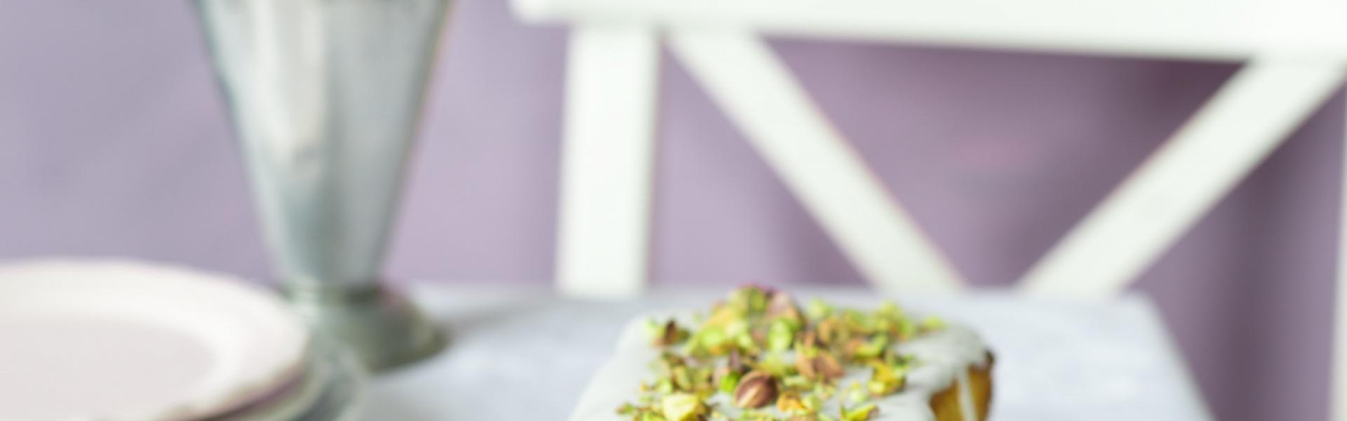 Mascarpone-Kuchen mit Himbeeren und Zuckerguss steht auf einem Kuchenteller.