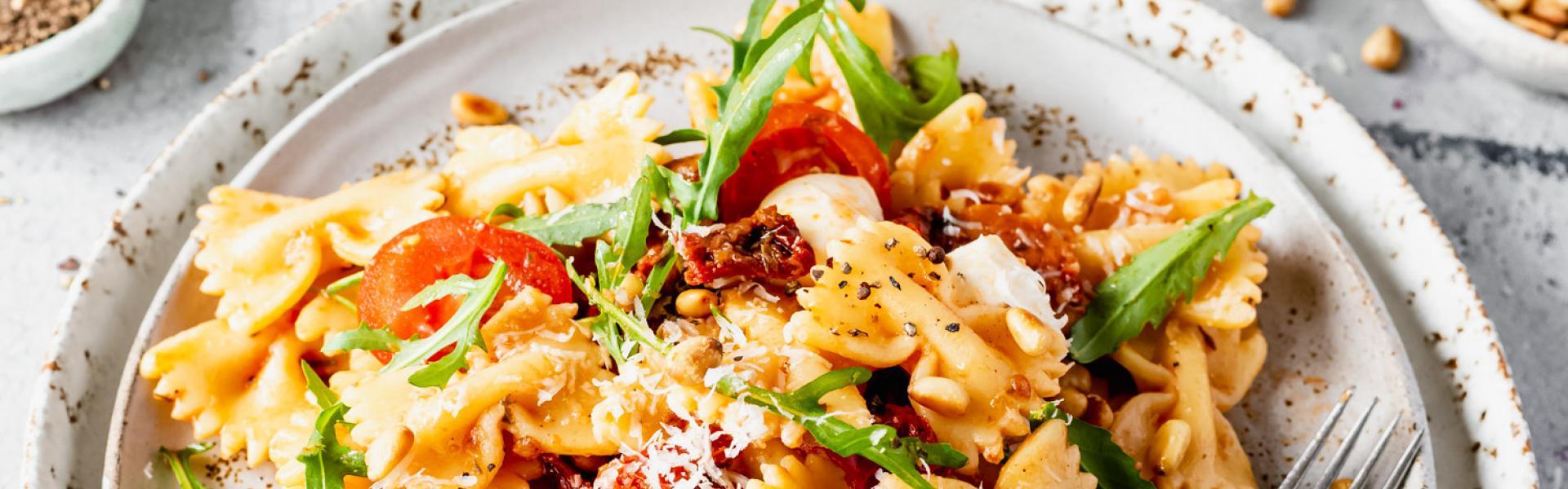 Nudelsalat mit getrockneten Tomaten, Rucola und Mozzarella auf einem Teller angerichtet.