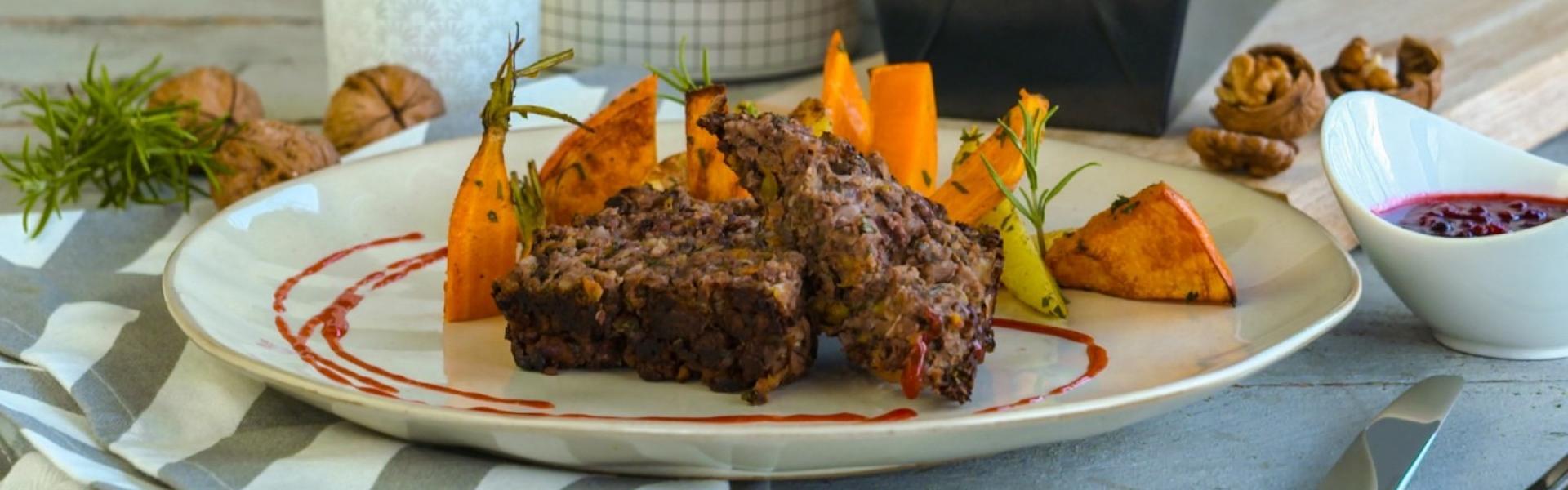 Zwei Scheiben Nussbraten mit Karotten und Kürbis auf einem Teller.