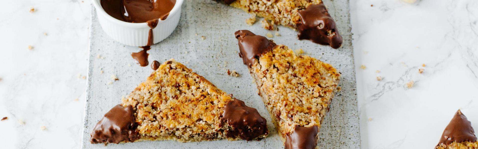 Kalorienarme Nussecken mit Schokolade auf Marmortisch.