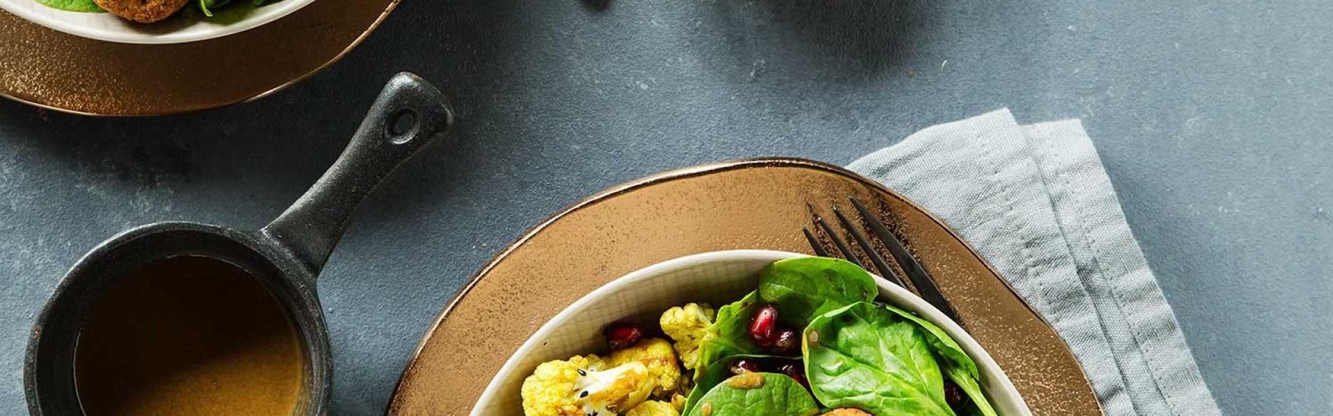Orientalische Buddha Bowl mit Falafel auf einem Tisch angerichtet.