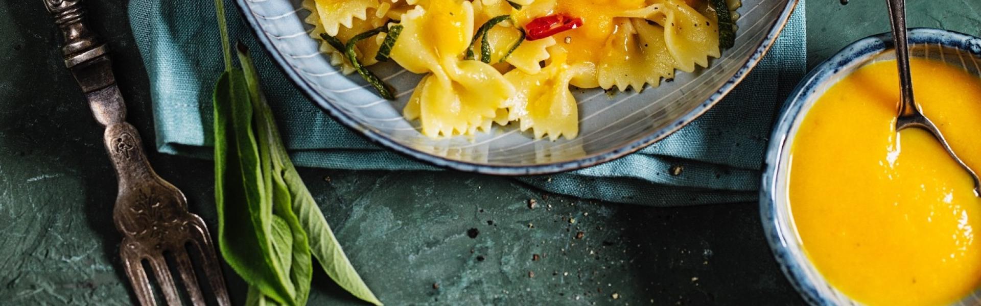 Farfalle in Pastasoße auf dunkelgrünem Teller in dunkelgrünem Setting.