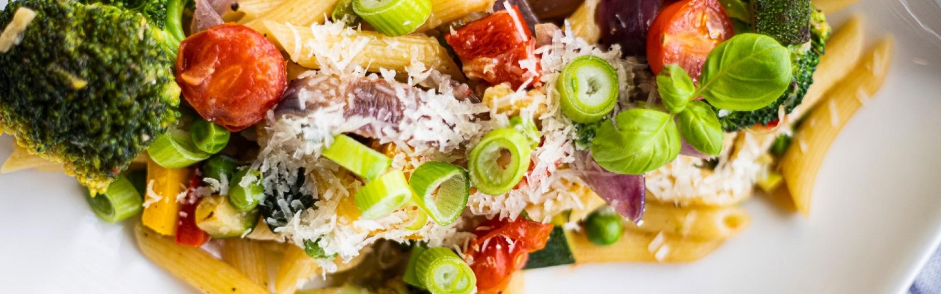 Pasta Primavera mit viel buntem Gemüse auf weißem Teller.