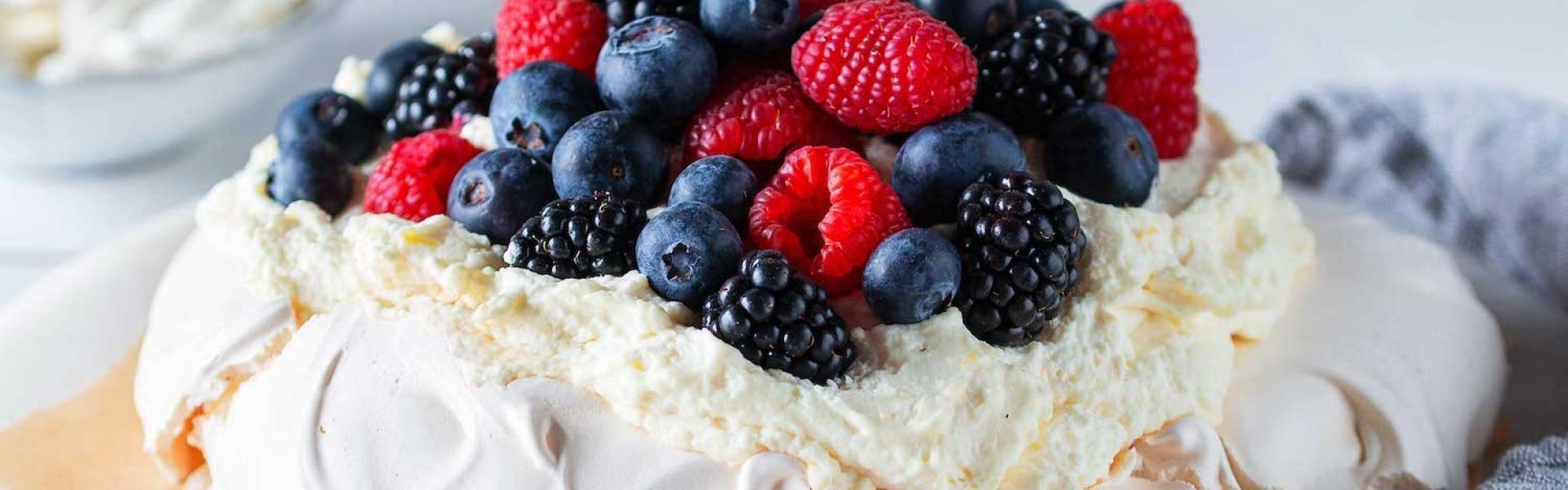 Pavlova mit Mascarpone auf einer Kuchenplatte.
