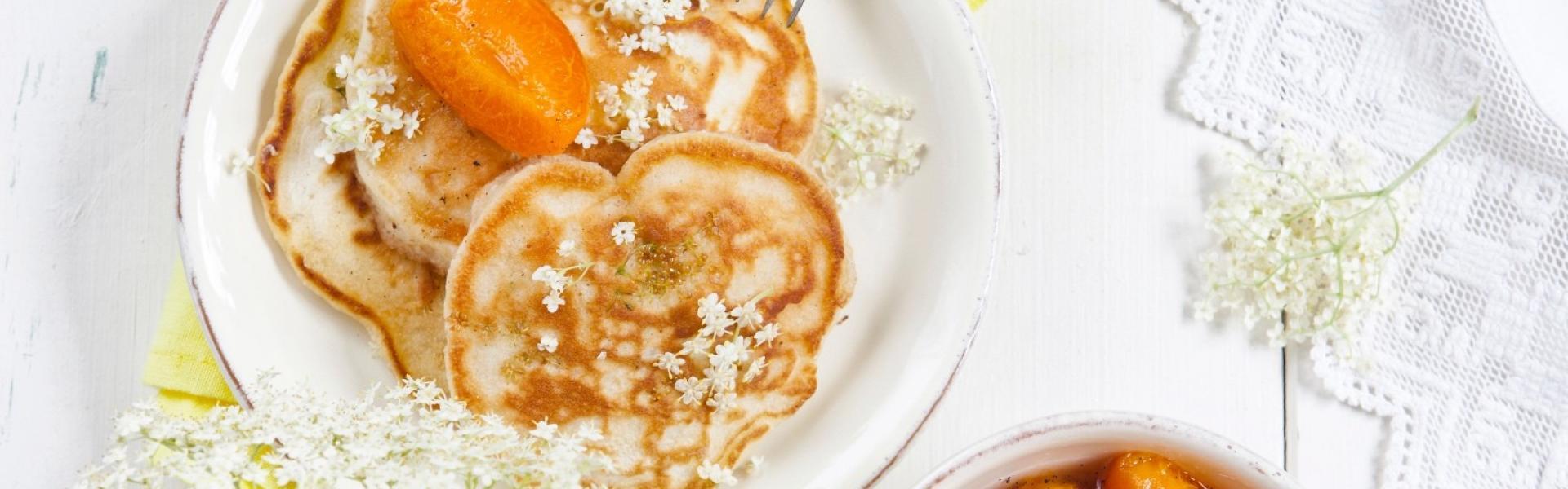 Pfannkuchen übereinandergestapelt auf einem Teller dazu Aprikosenkompott.