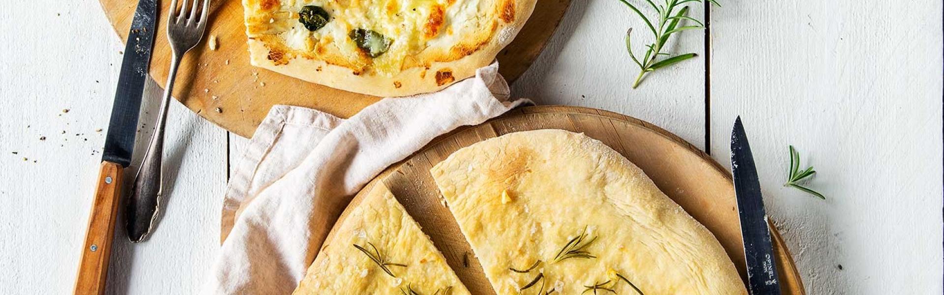 Zwei verschiedene Pizza Bianca auf weißem Holztisch.