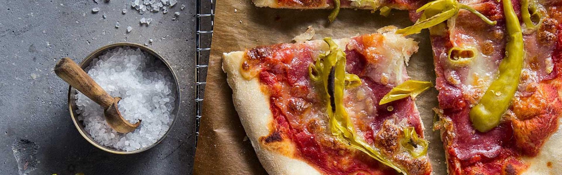 Pizza Diavolo angeschnitten auf einem Stück Backpapier.