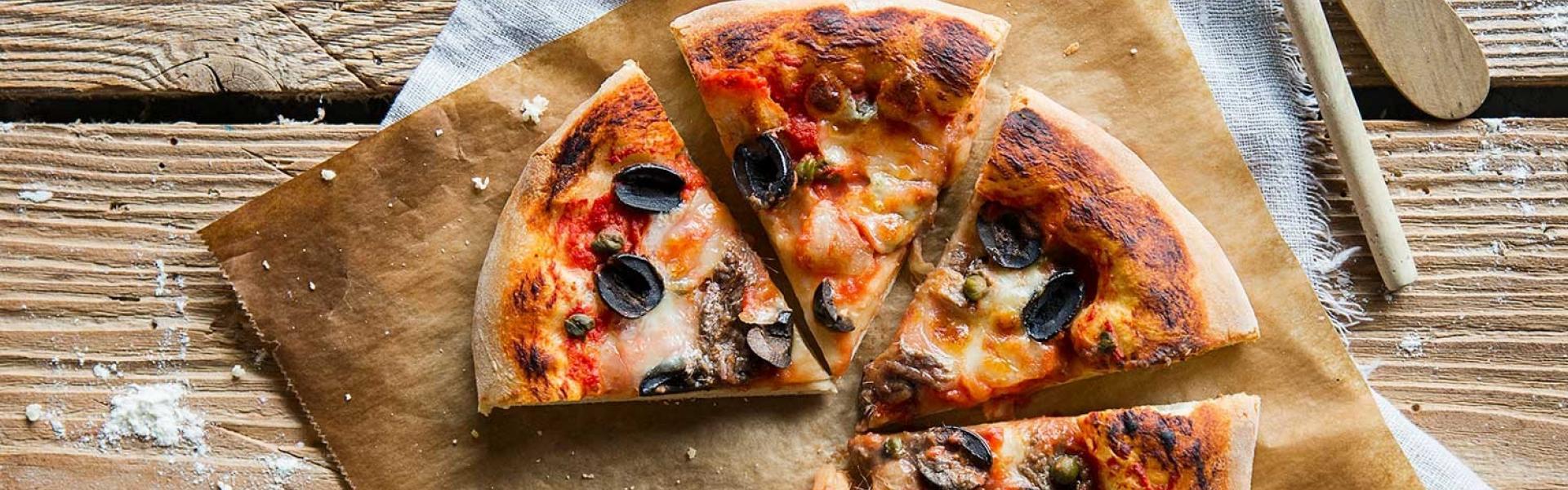 Angeschnittene Pizza Napoli auf einem Stück Backpapier, daneben Kapern.