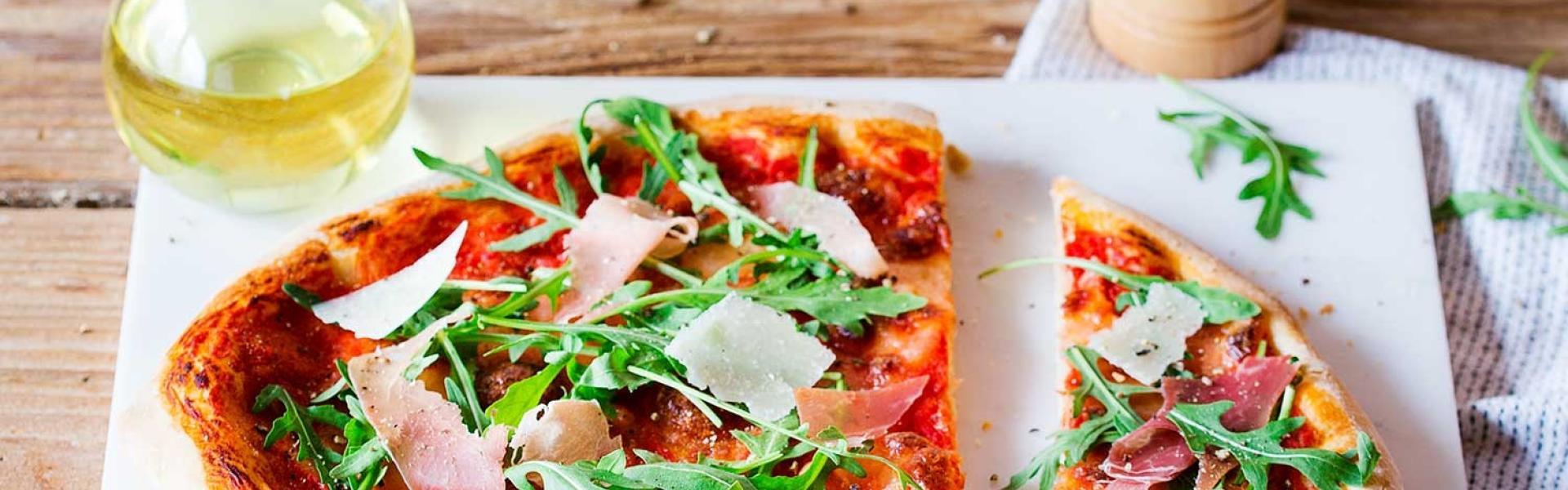 Pizza Parma mit Rucola halbiert auf Marmorplatte auf Holztisch.