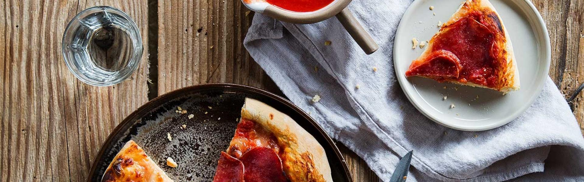 Pizza Salami angeschnitten auf einem Teller.