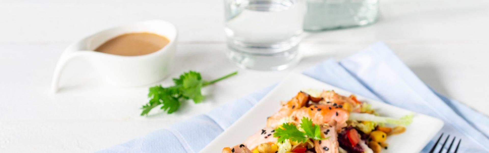 Weiße Platte mit Pulled Lachs Salat angerichtet.