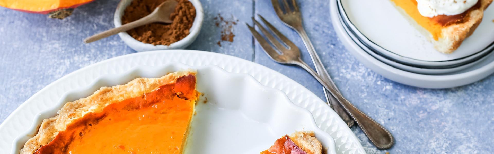 Pumpkin Pie auf einem Tisch mit Kürbissen, Püree und Sahne angerichtet.