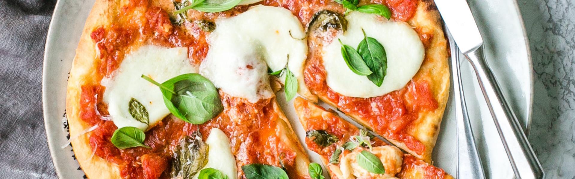 Pizza Margherita mit einem Pizzateig ohne Hefe auf Teller und grauer Serviette.