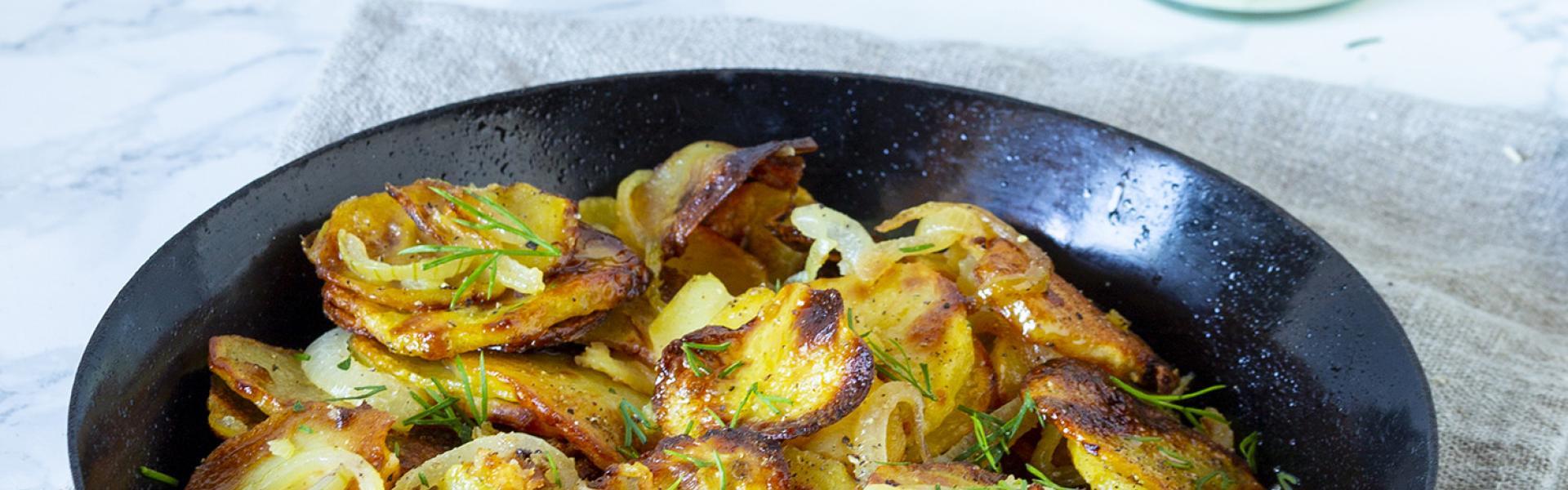 Bratkartoffeln aus rohen Kartoffeln in einer Gusseisenpfanne auf einem Tisch.