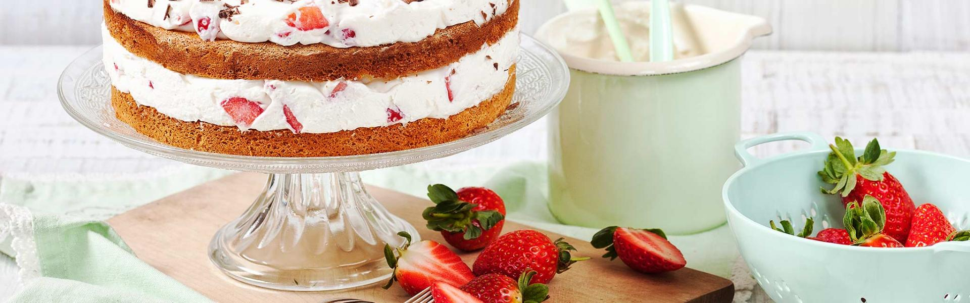 Erdbeer-Joghurt-Torte steht auf einer Etagere auf einem gedeckten Tisch.
