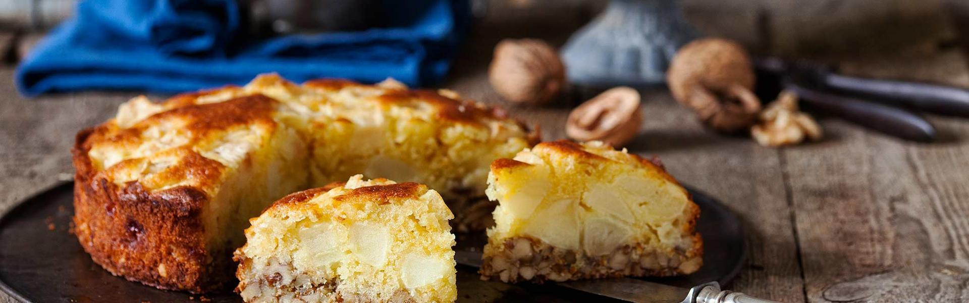 Apfel-Walnuss-Kuchen auf einer Kuchenplatte angeschnitten.