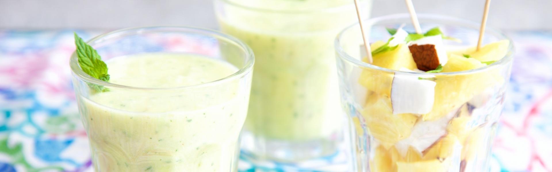 Ananas Smoothie in zwei Gläsern mit Ananaswürfeln in einem weiteren Glas