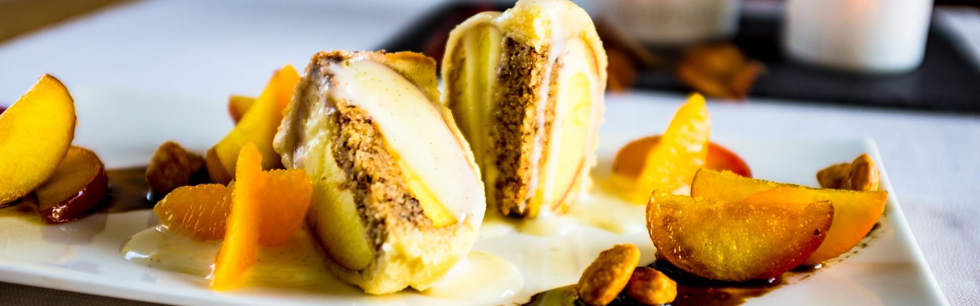 Apfel im Schlafrock halbiert und auf Teller mit Vanillesoße und Orangenfilets angerichtet.