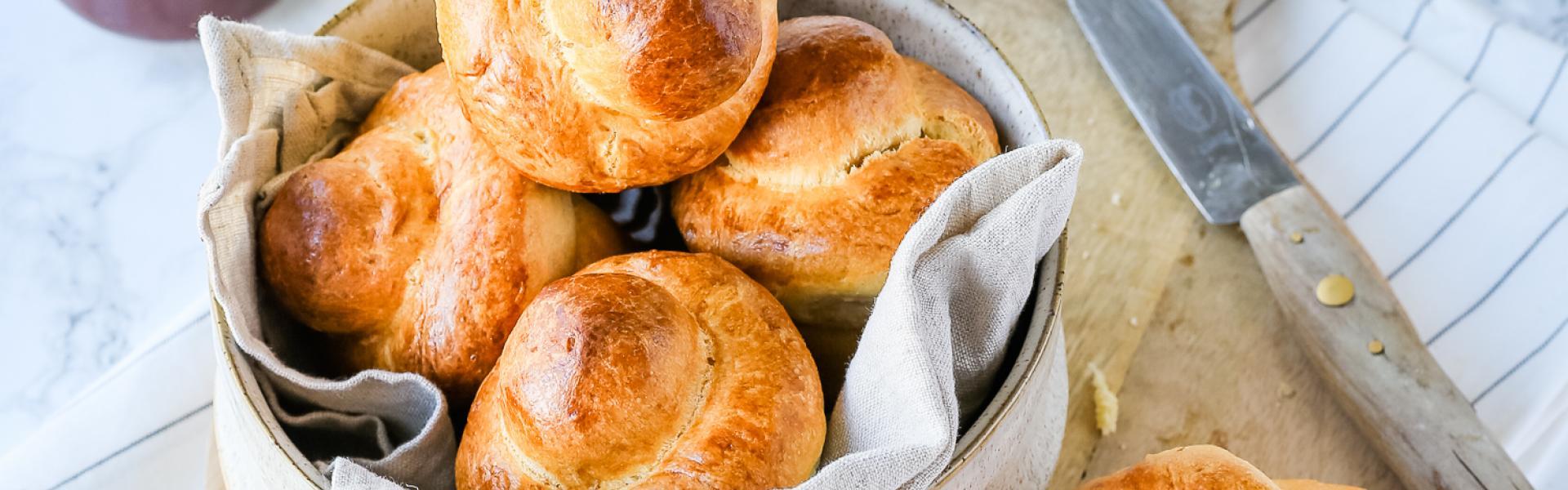 Mehrere Brioches liegen in einnem Körbchen auf einem gedeckten Tisch mit Nougatcreme und Milch.