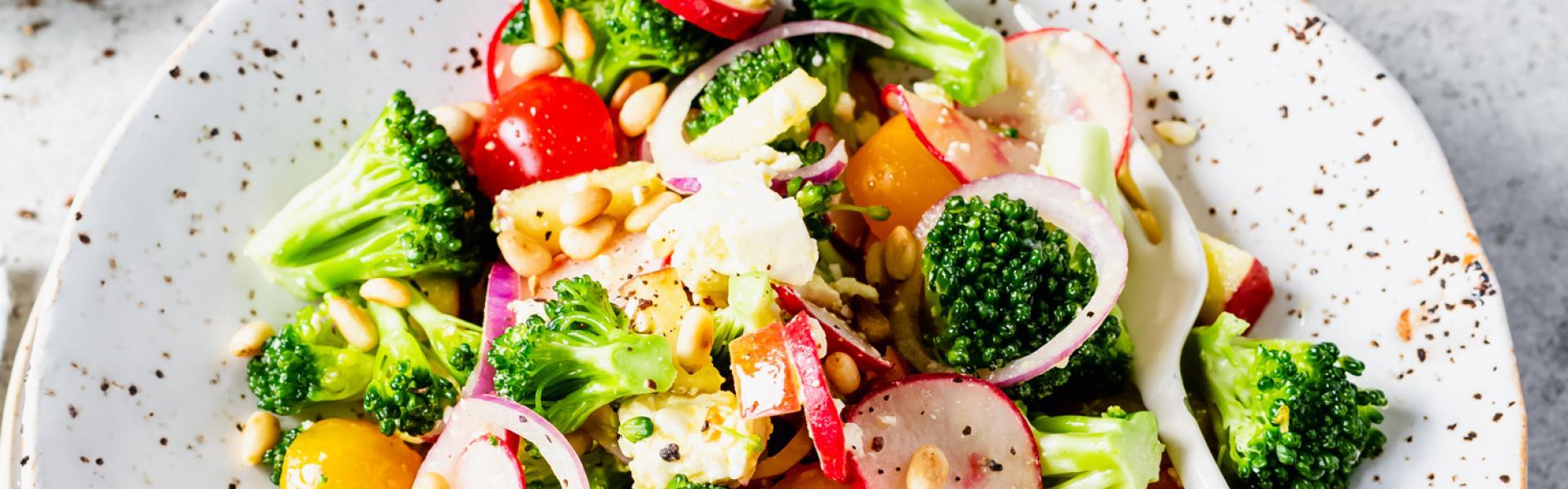 Bunter roher Brokkolisalat auf einem Teller mit angelehnter Gabel.