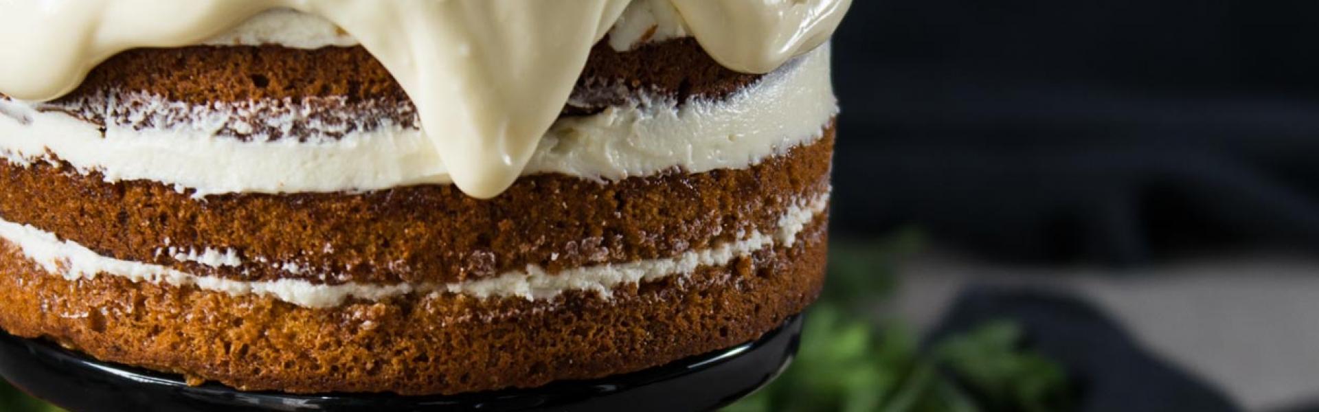 Carrot Cake auf schwarzer Tortenplatte mit Möhren dekoriert.