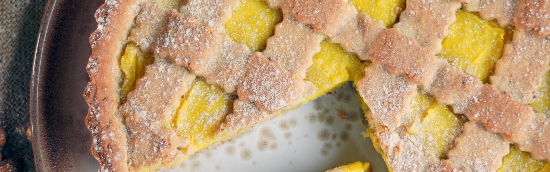 Angeschnittene Zitronentarte auf hellem Holztisch mit vielen Zitronen.