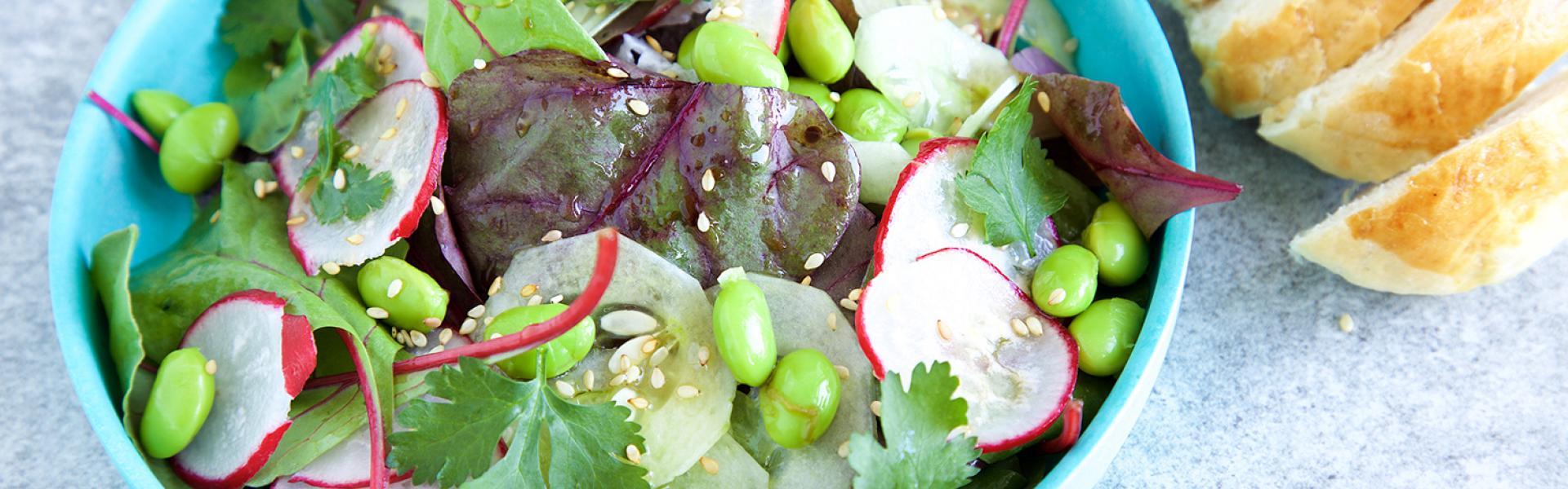 Edamame-Radieschen-Salat in einer Schüssel angerichtet. Daneben aufgeschnittenes Brioche.