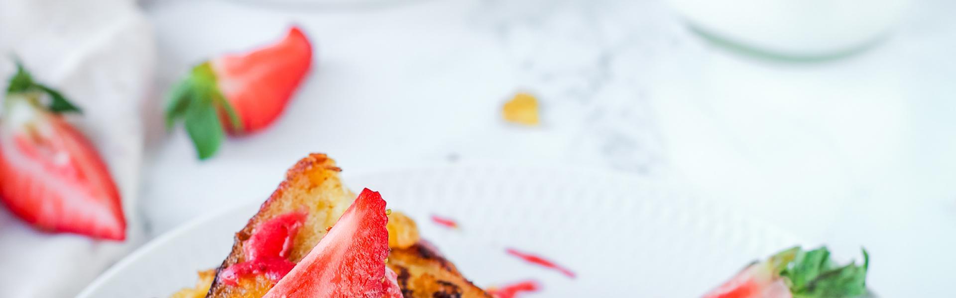 Mehrere French Toast mit Erdbeermus liegen auf einem Teller aufgeschnitten und mit Mus bekleckst.