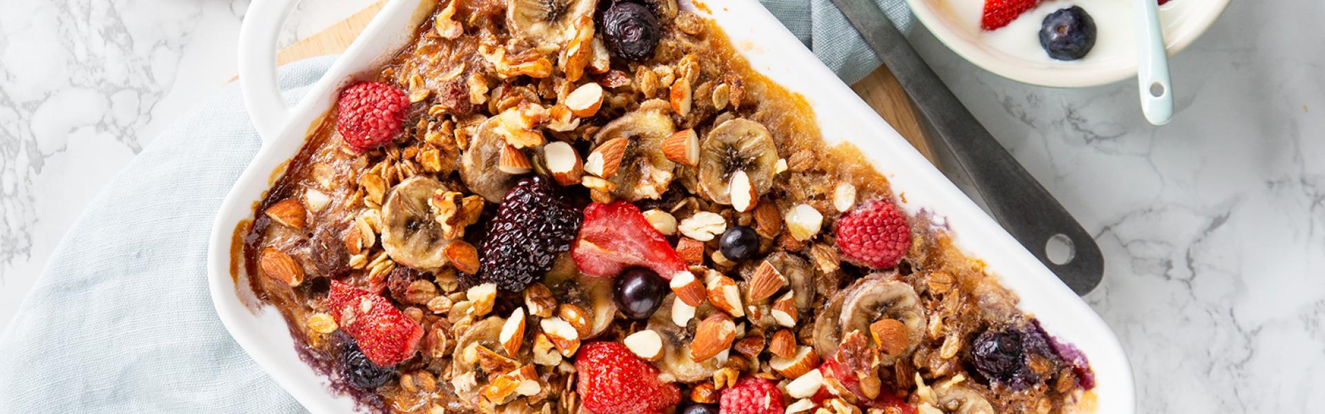 Frühstücksuaflauf steht in der Form auf einem Tisch. Daneben Joghurt und Beeren.