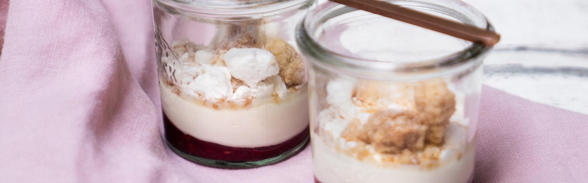 Zwei Gläser Himbeer-Mascarpone-Dessert mit Streuseln auf rosafarbener Tischdecke.