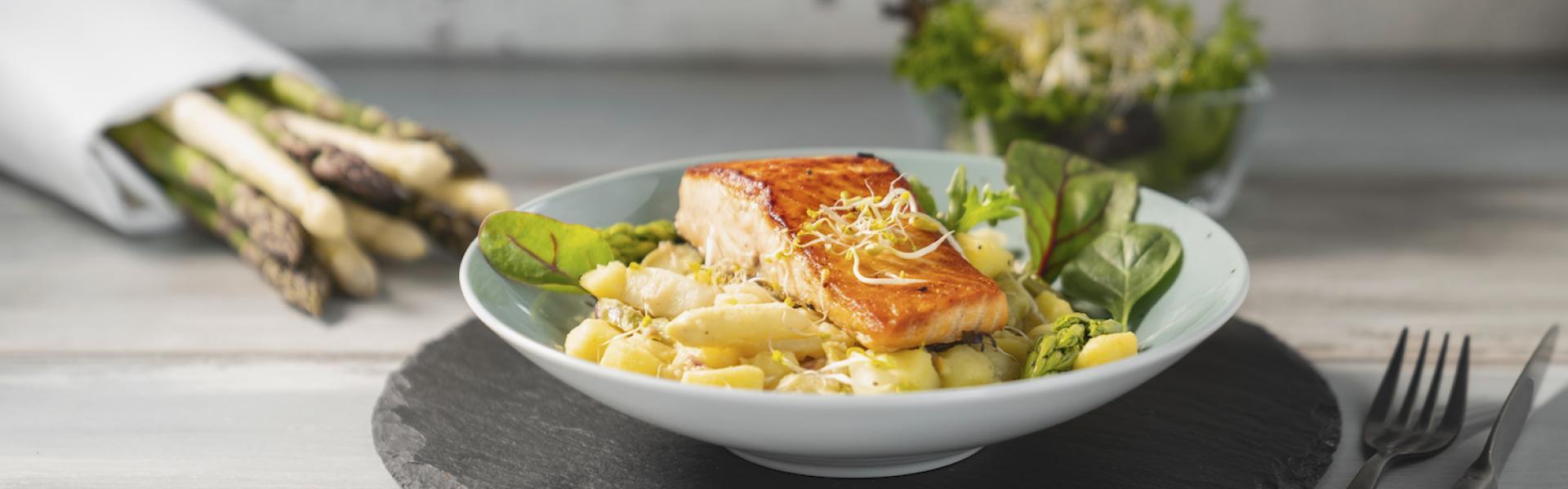 Ein Teller Kartoffel-Spargel-Salat auf weißem Holztisch.