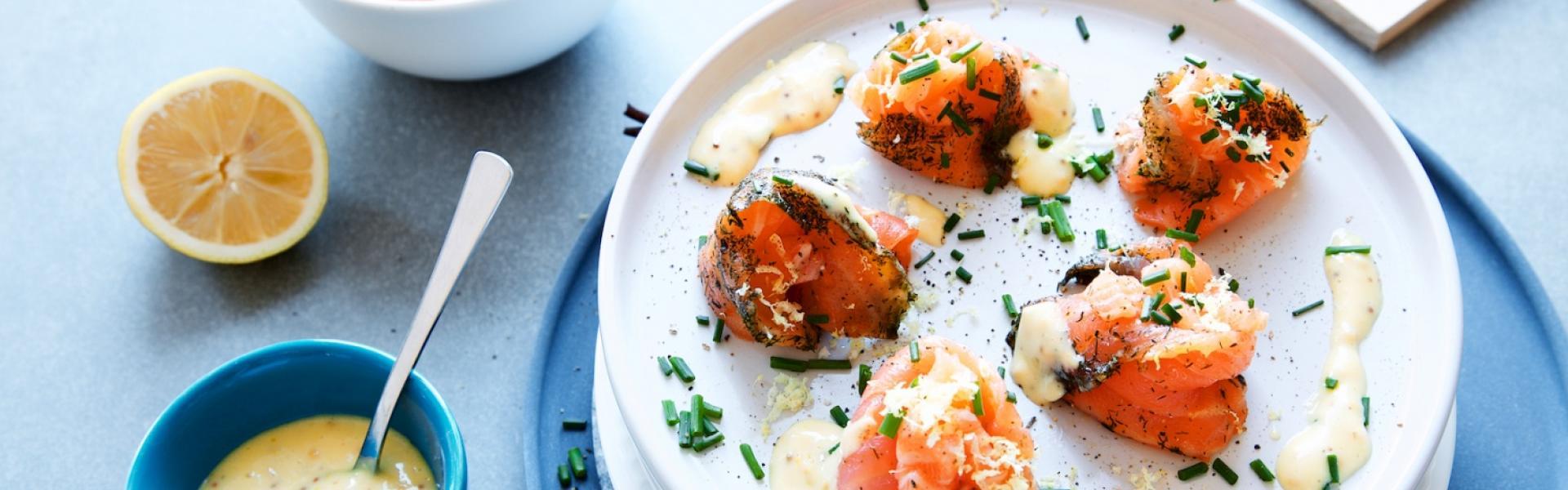Lachsröllchen auf Teller angerichtet und Mayonnaise serviert