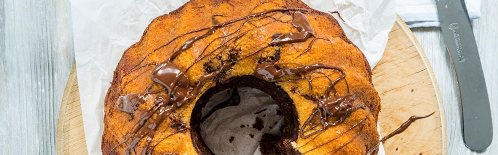 Marmorkuchen saftig und mit Schokoladenglasur steht angeschnitten auf einem Tisch.