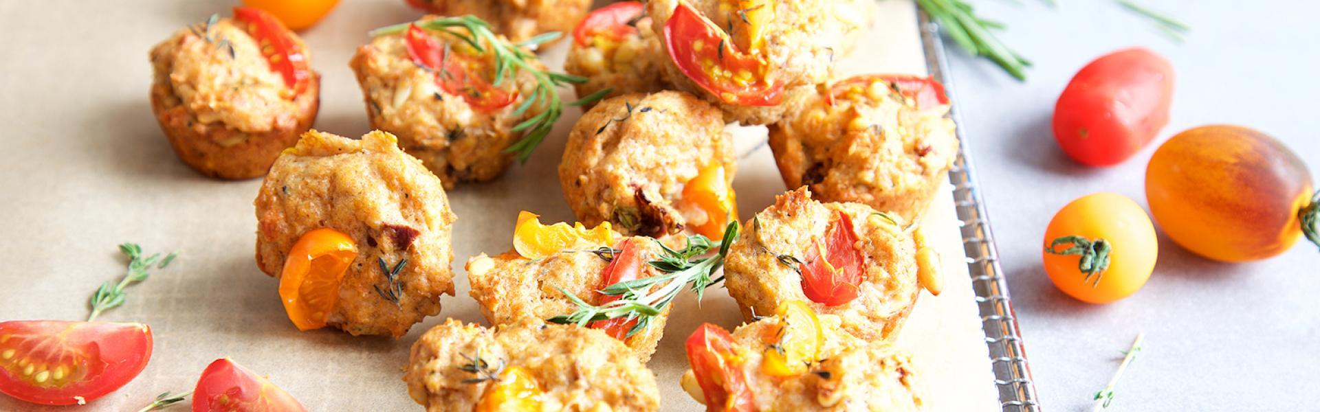 Mehrere Mini-Muffins mit Tomaten auf einem Backblech.