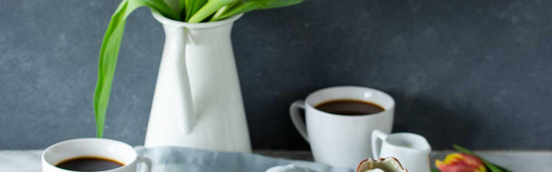 Zwei Stücke Osterkuchen vom Blech auf Tellern, die auf einem gedeckten Kaffeetisch stehen.