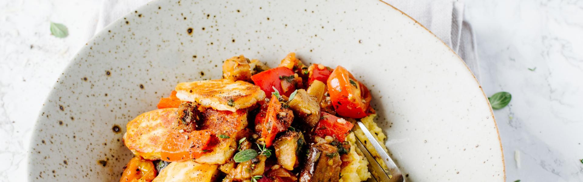 Pesto-Polenta mit Halloumi und Gemüse auf einem Teller angerichtet.