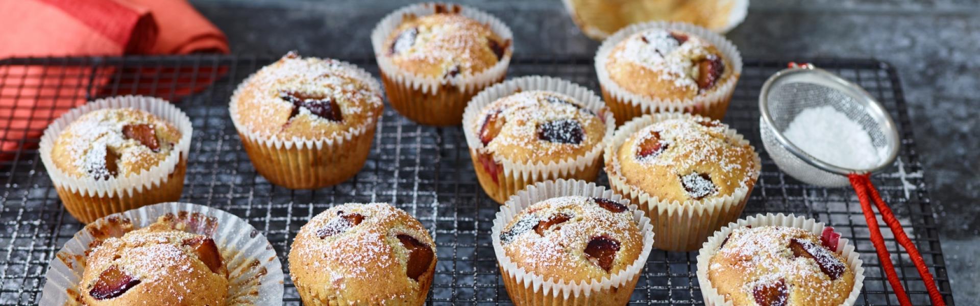 Zehn Pflaumen-Muffins auf Kuchengitter und Puderzuckersieb