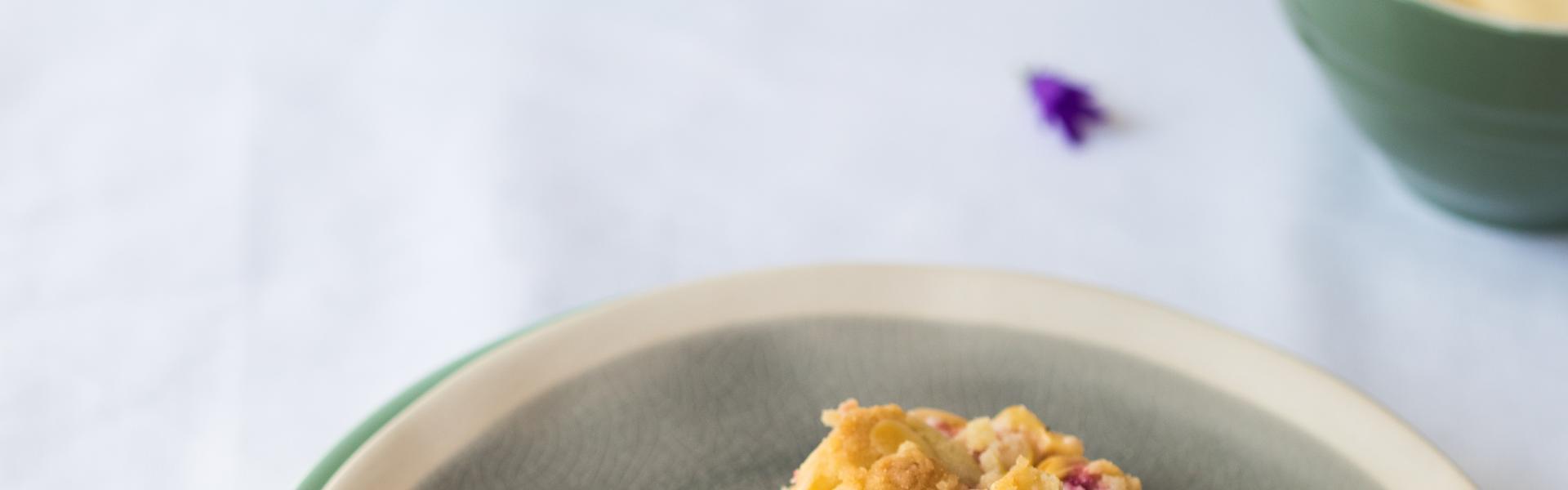 Ein Stück Pflaumenkuchen mit Pudding liegt auf einem Teller.