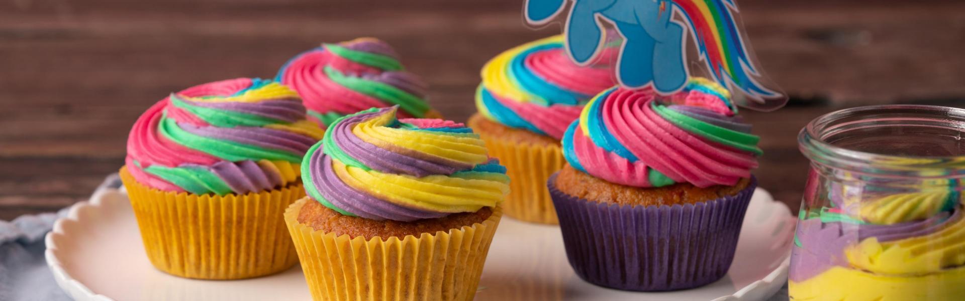 Regenbogen-Cupcakes mit Rainbow-Dash-Topper auf weißem Teller.