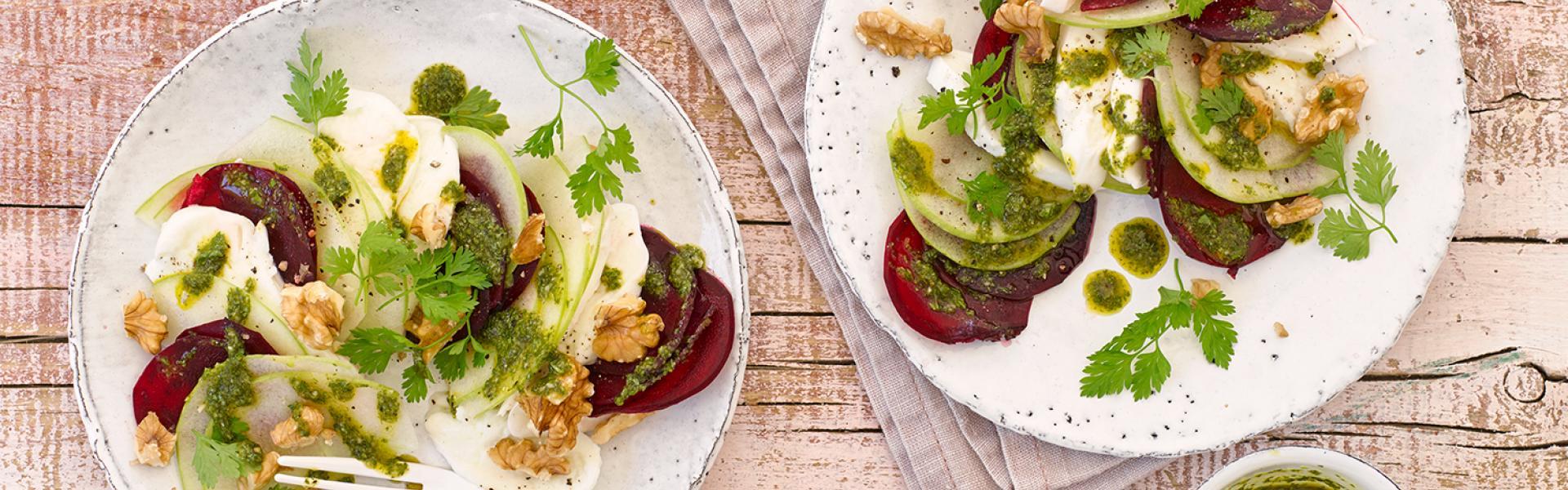 Rote-Bete-Mozzarella-Salat auf zwei Tellern angerichtet.