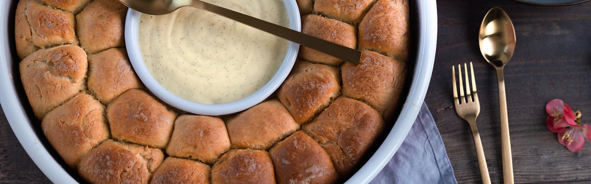 Schoko-Monkey-Bread mit Vanillesoße in einer Backform.