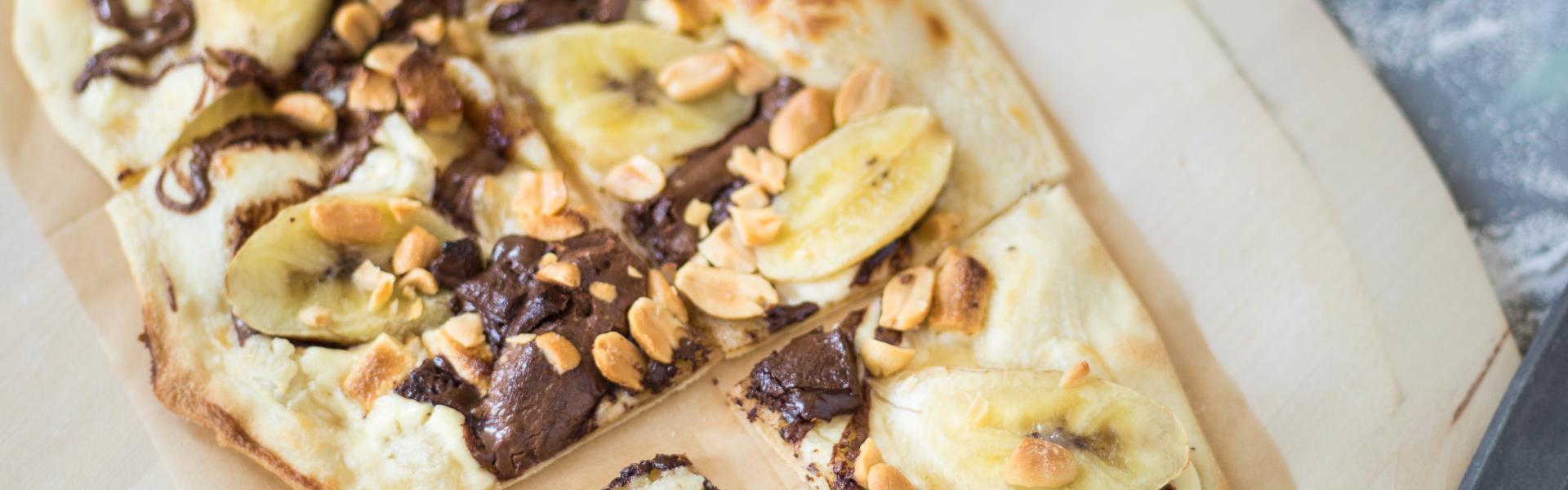 Süßer Flammkuchen mit Nutella und Banane liegt auf einem Stück Backpapier.