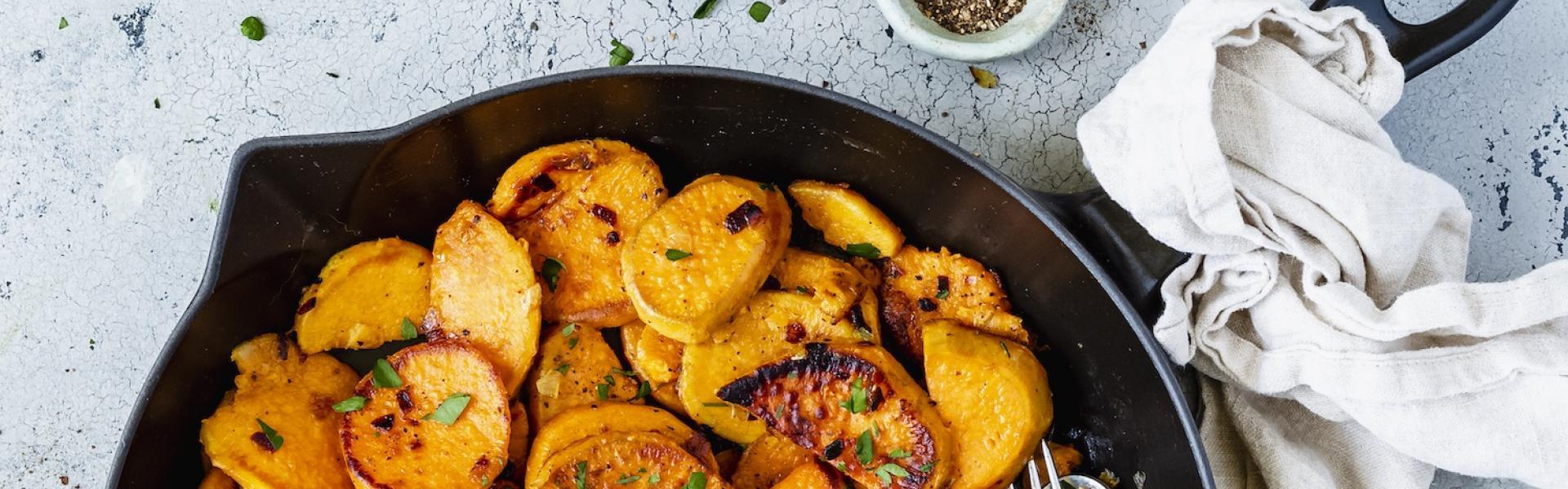 Süßkartoffel-Bratkartoffeln in einer Gusseisenpfanne mit Tuch.