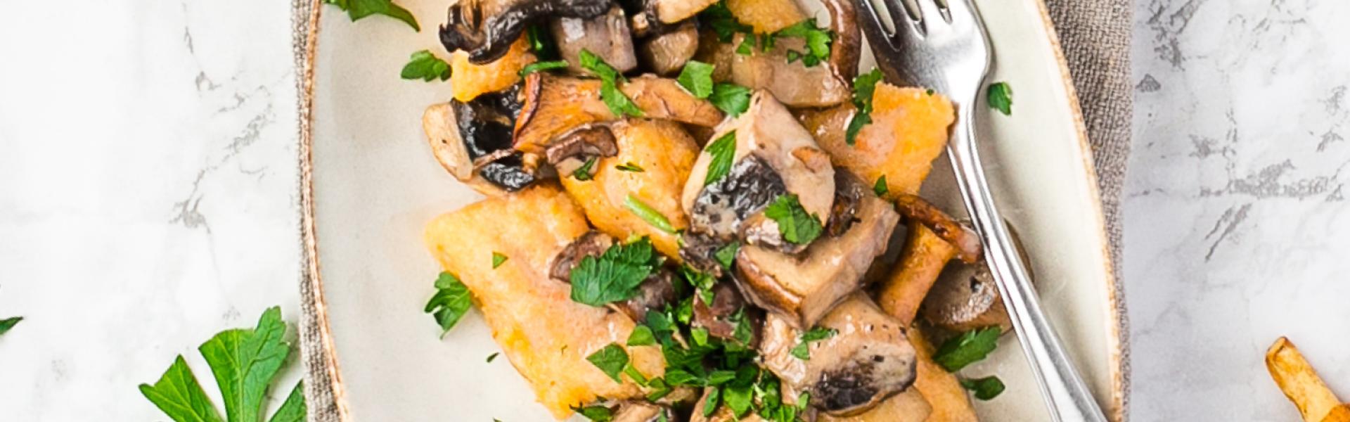 Süßkartoffelgnocchi mit Pilzragout auf einem Teller angerichtet.