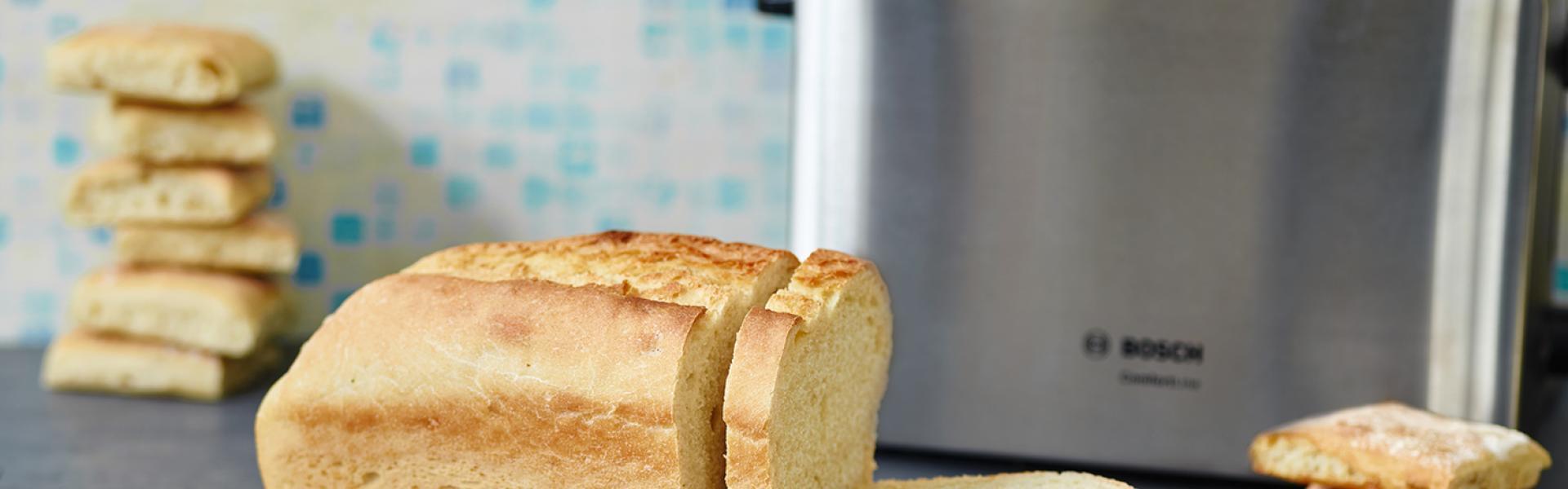 Auf einem Holzbrett steht der angeschnittene Laib vom Toastbrot Rezept. Im Hintergrund ein Toaster.