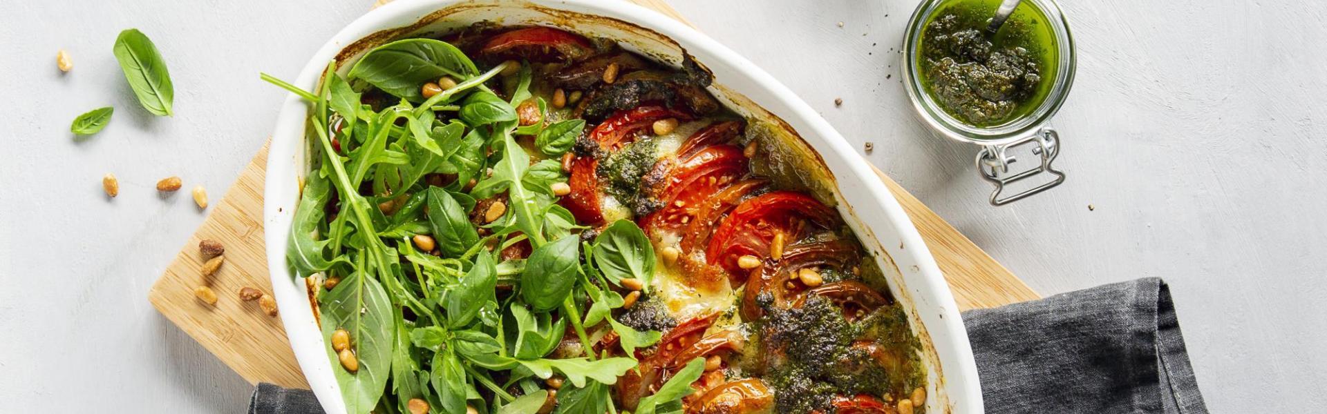 Tomate-Mozzarella-Auflauf mit Rucola in weißer Auflaufform.