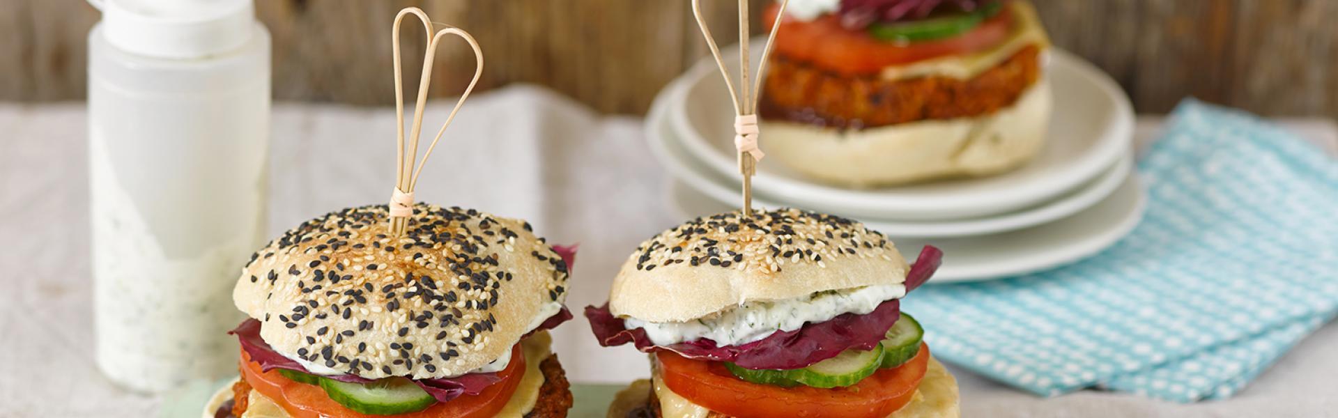 Drei vegetarischer Burger auf einem Brettchen und einem Teller angerichtet.