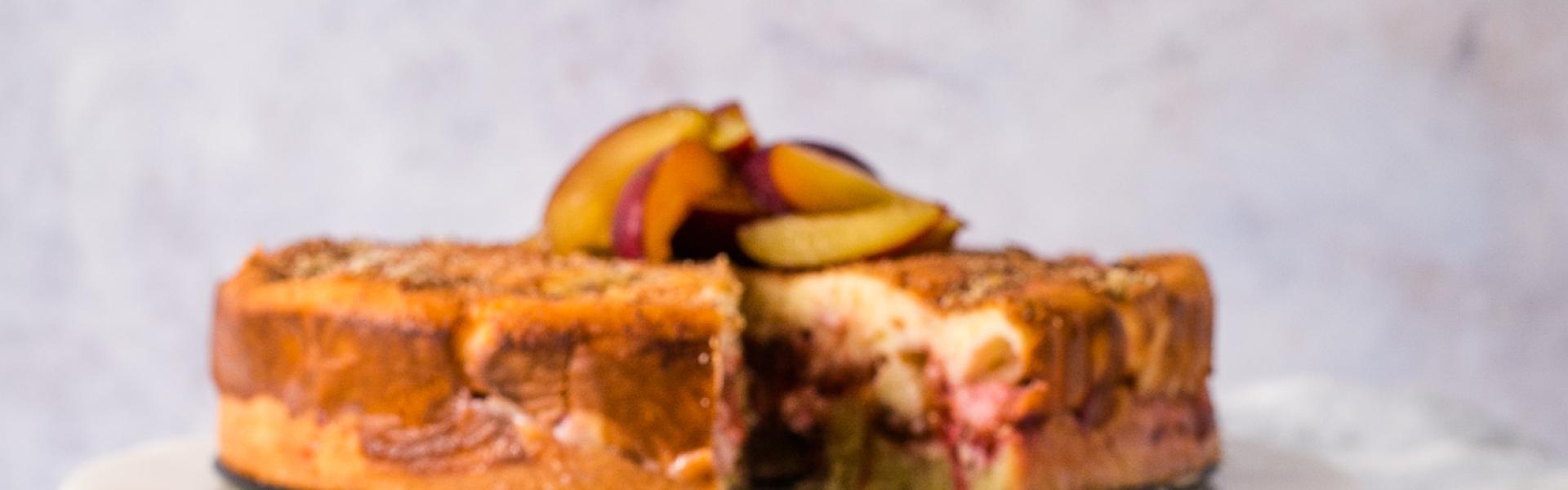 Zwetschgen-Quark-Kuchen angeschnitten auf einer Etagere. Ein Stück liegt auf einem Kuchenteller davor.